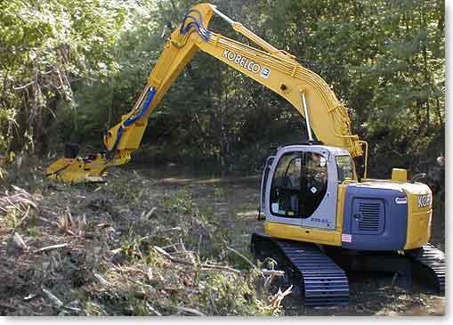 excavator crawling up streambed while mulching drainage vegetation
